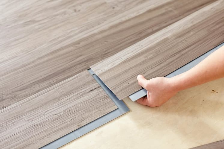 man installing vinyl flooring