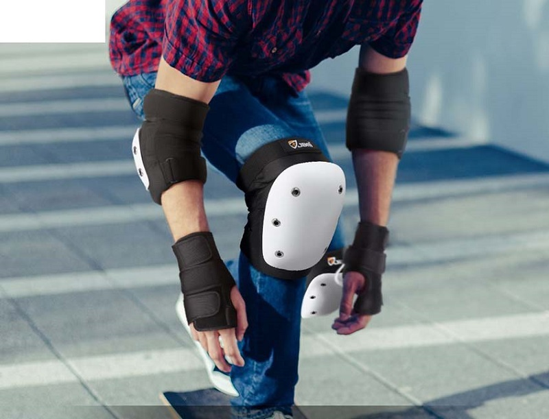 picture of a person riding skateboard on a street with safety items