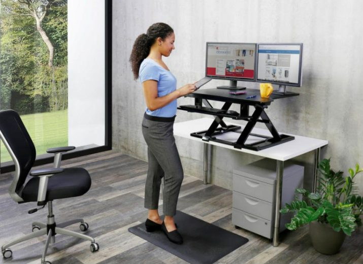 Beautiful office women working while standing Ergotron