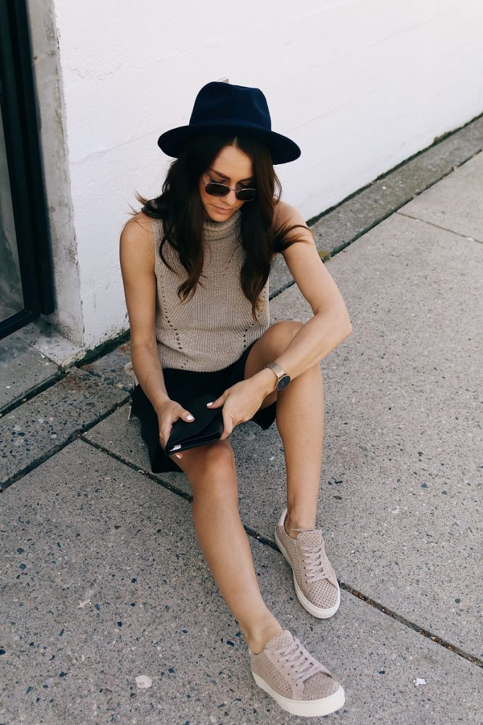 picture of a woman sitting on the concrete beside a white wall, wearing black hat, beige top, black shorts and beige flat lace up shoes