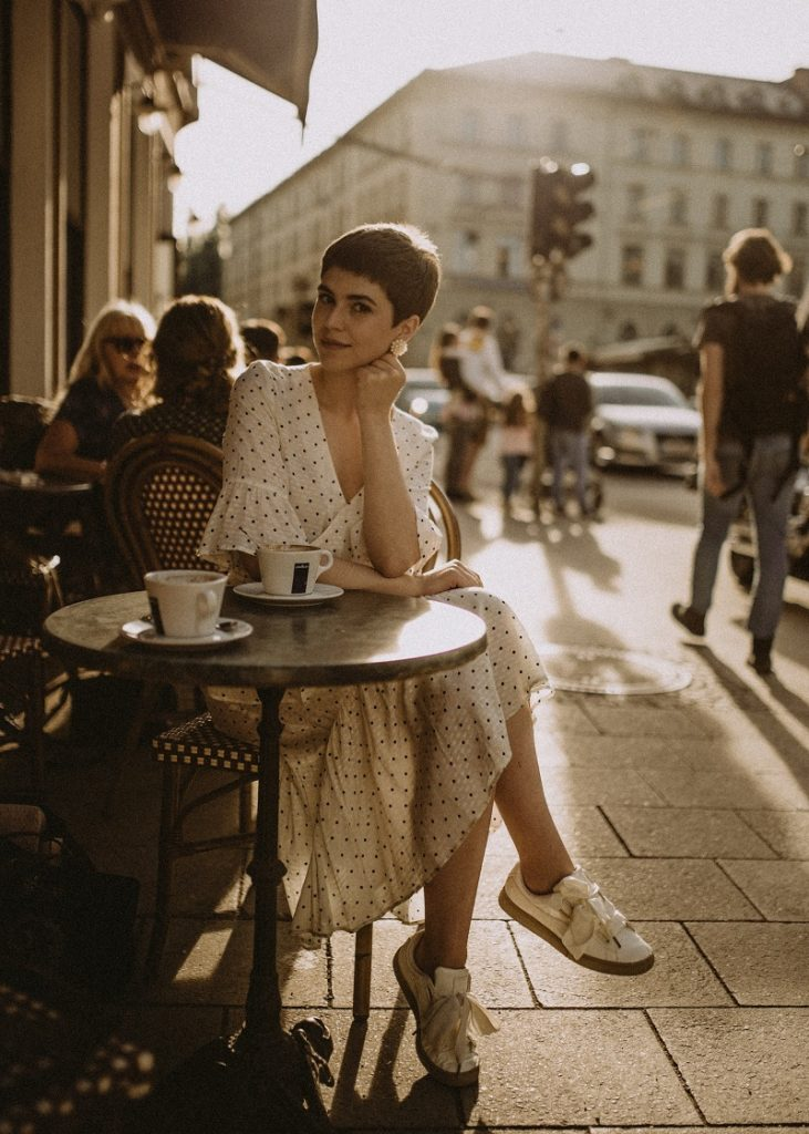 picture of a stylish woman sitting in a coffeshop beside a street