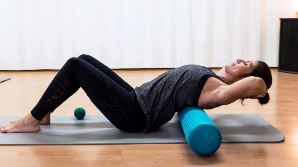 female exercising on a pink foam roller